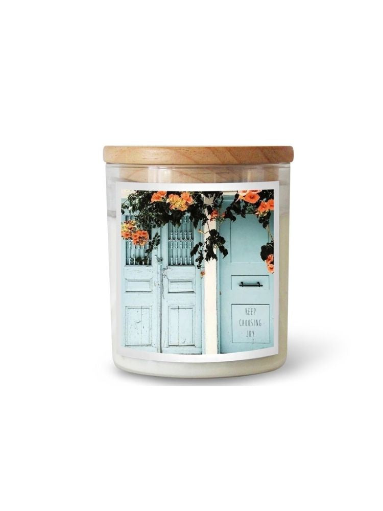 Candle with a picture of a begonias and blue doors.