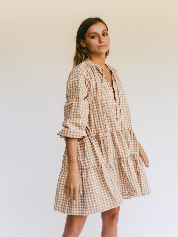 Young woman posing on side view with checked dress