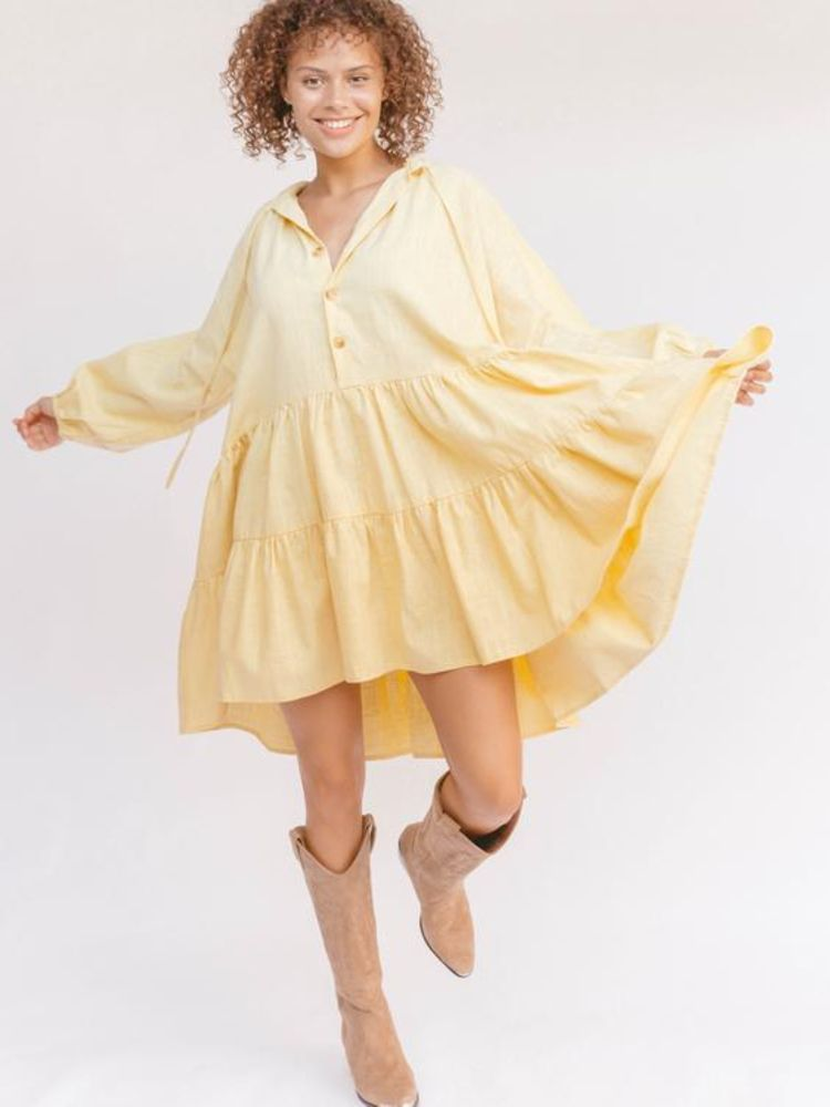 Lady wearing a yellow dress and brown boots posing
