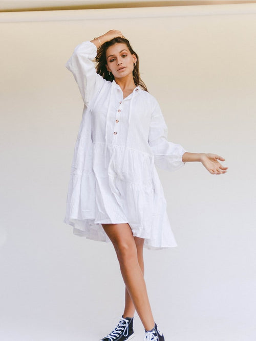 Young woman models The Lullaby Club Avalon Smock Dress in white