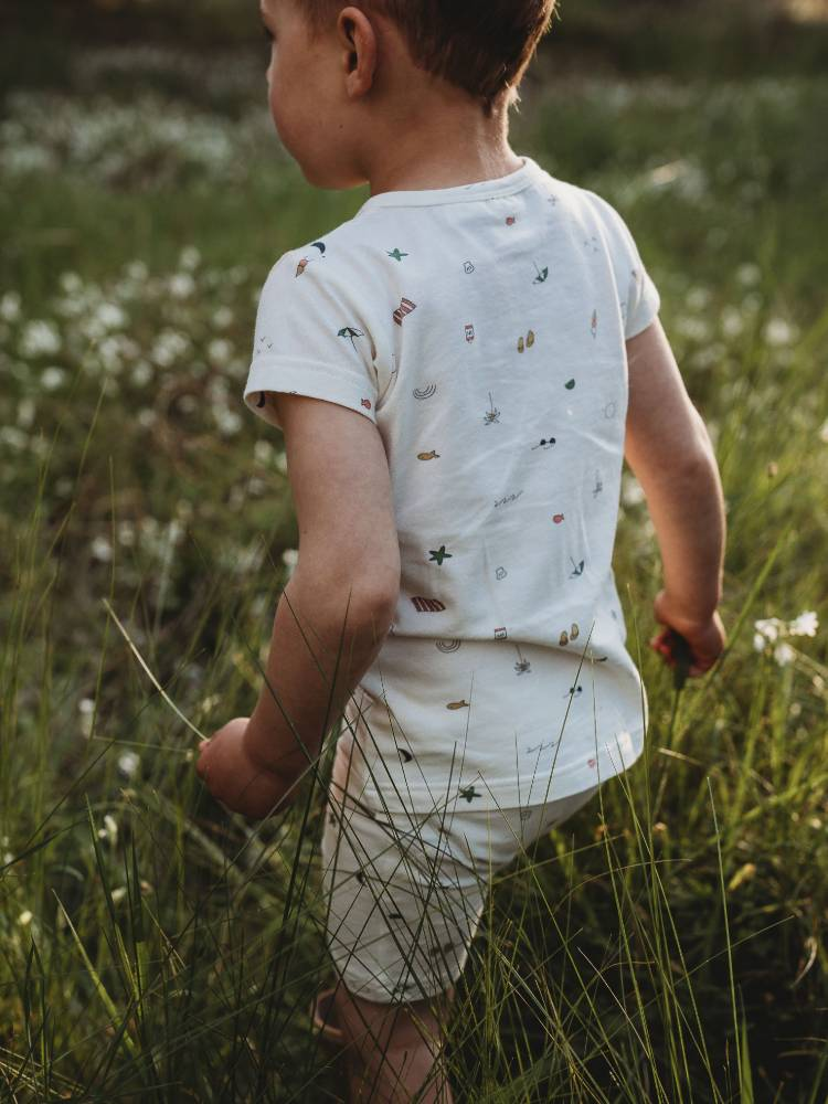 Little boy wearing white pajamas walking through tall grass
