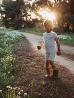 Little boy wearing white pajamas walking on the side of a dirt road