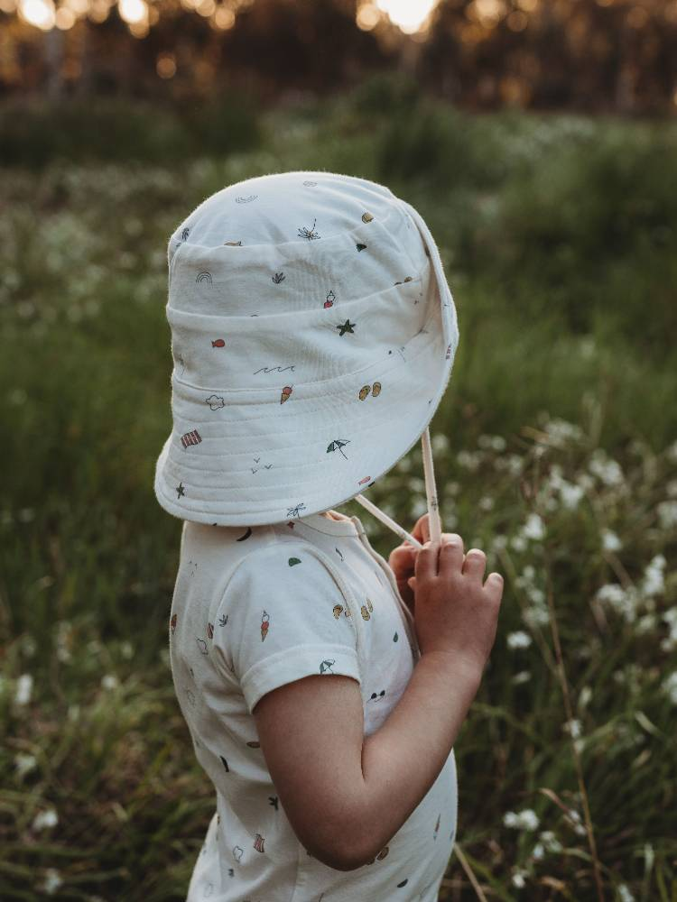 boy in sunhat from the rest against green background
