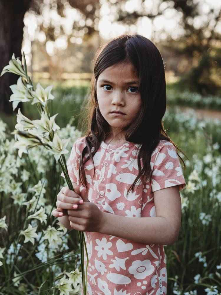 Little girl holding long stemmed flower