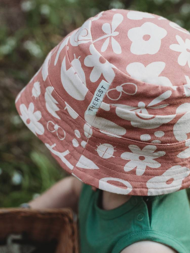 Pink and white patterned hat on a small child