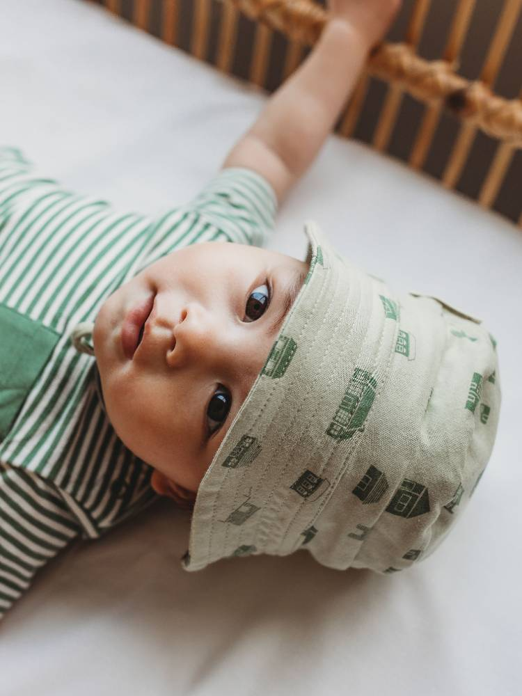 Baby lying in a cot wearing a green hat