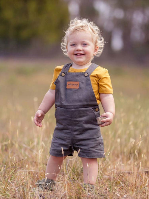 Baby in a field wearing the Wild Island Apparel Wilding Overalls in Ash Blue