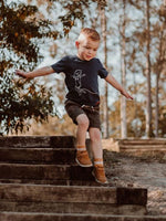 Young boy runs down the garden stairs in a Wild Island Apparel T-Shirt