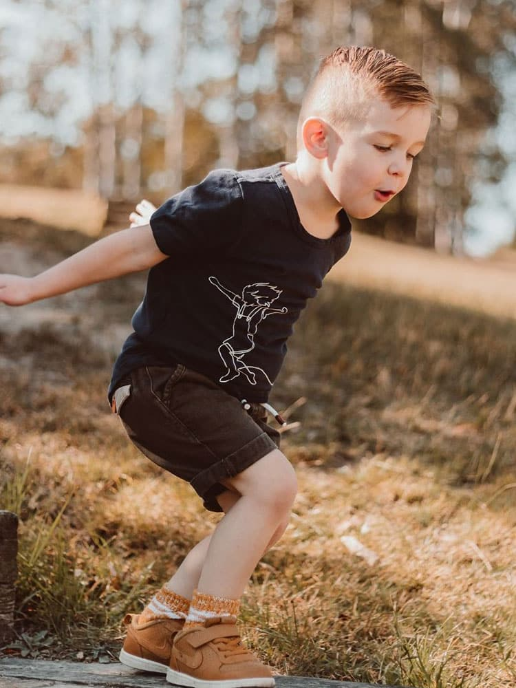 Young boy runs plays in a Wild Island Apparel T-Shirt