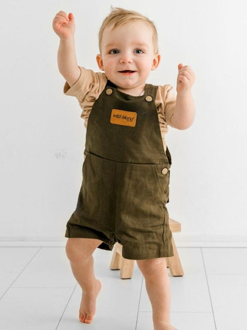 Baby wears the Wildings Overalls in olive by Wild Island Company