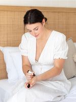 Young woman in white dress applies a Willelaine Aromatherapy roll on to her wrists