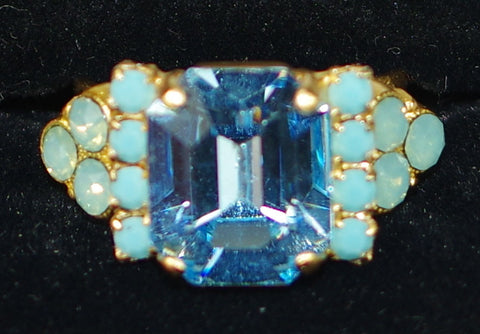 "MARIANA RING CINDY: blue, pacific opal stones, center stone = 1/2"" in yellow gold setting, adjustable size band"