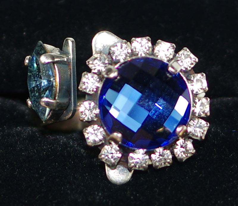 "MARIANA RING OCEAN: blue, clear stones in 1.25"" wide silver setting, adjustable size band"