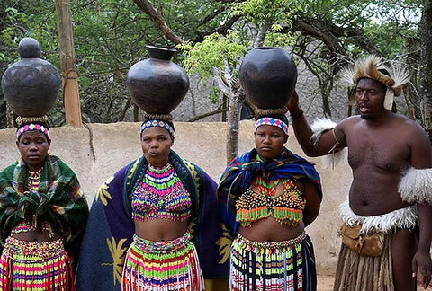 African tribe wearing waist beads and carrying water bowls on top of their heads