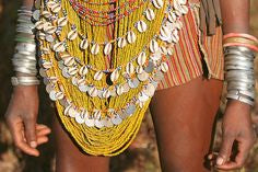 woman adorned in waist beads and bracelets