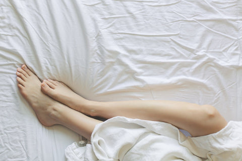 feet on white bedsheet