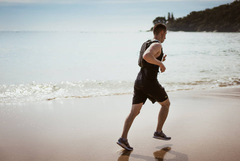 Man running in beach with earphones on