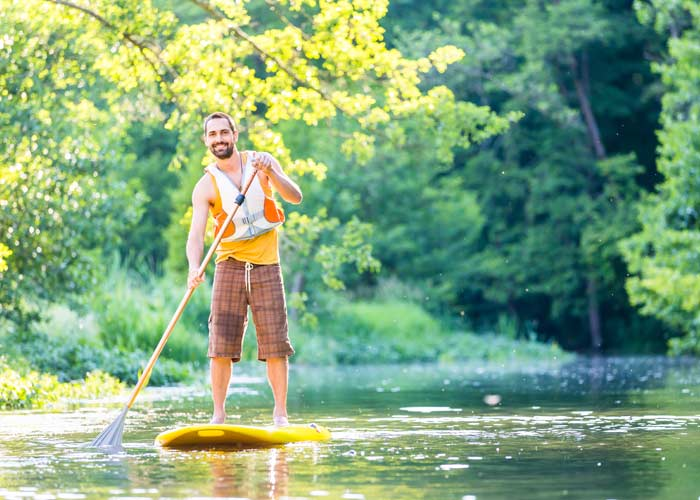 Stand up paddle-boarder wearing buoyancy aid