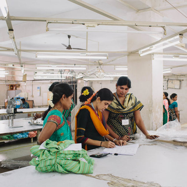 three women discuss fabric inside the India factory