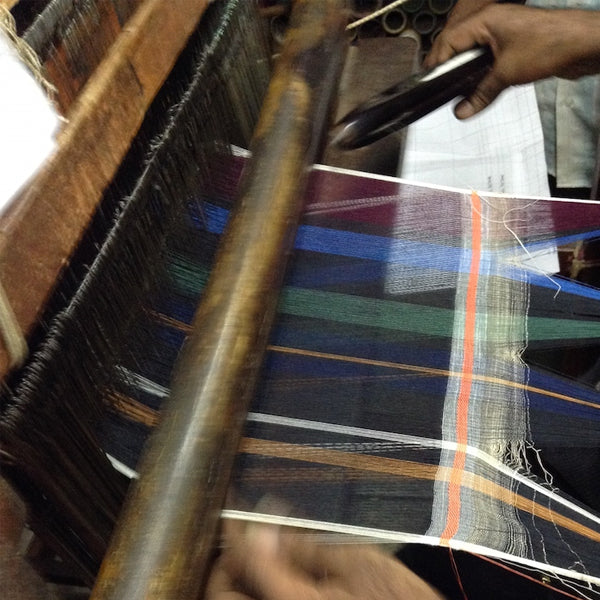 worker in India weaving fabric on a loom