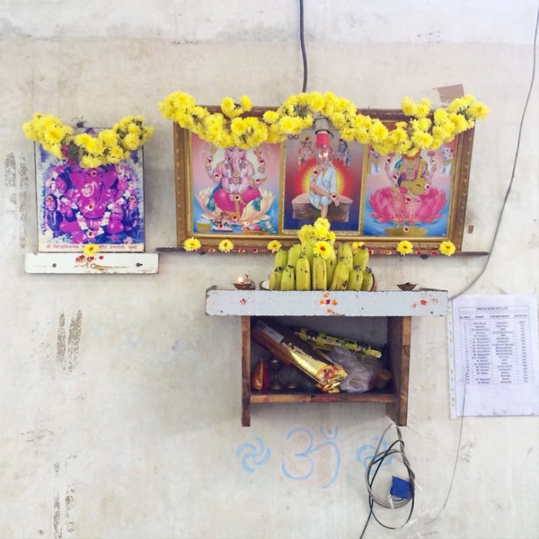 hindu shrine with fruit offerings inside of textile factory