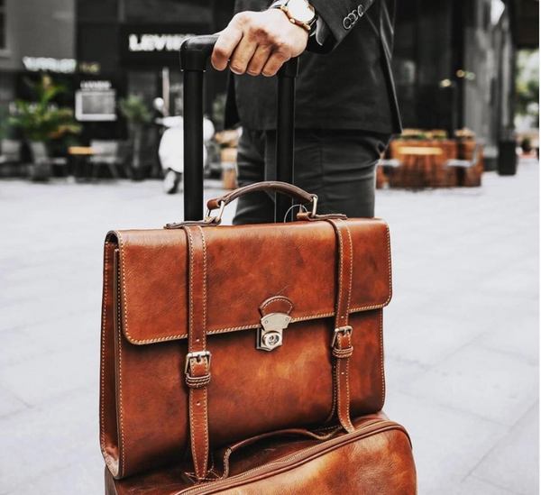 Seneca briefcase backpack on top of matching cognac coloured suitcase, led by man in black blazer with dark dress wearing Rolex.
