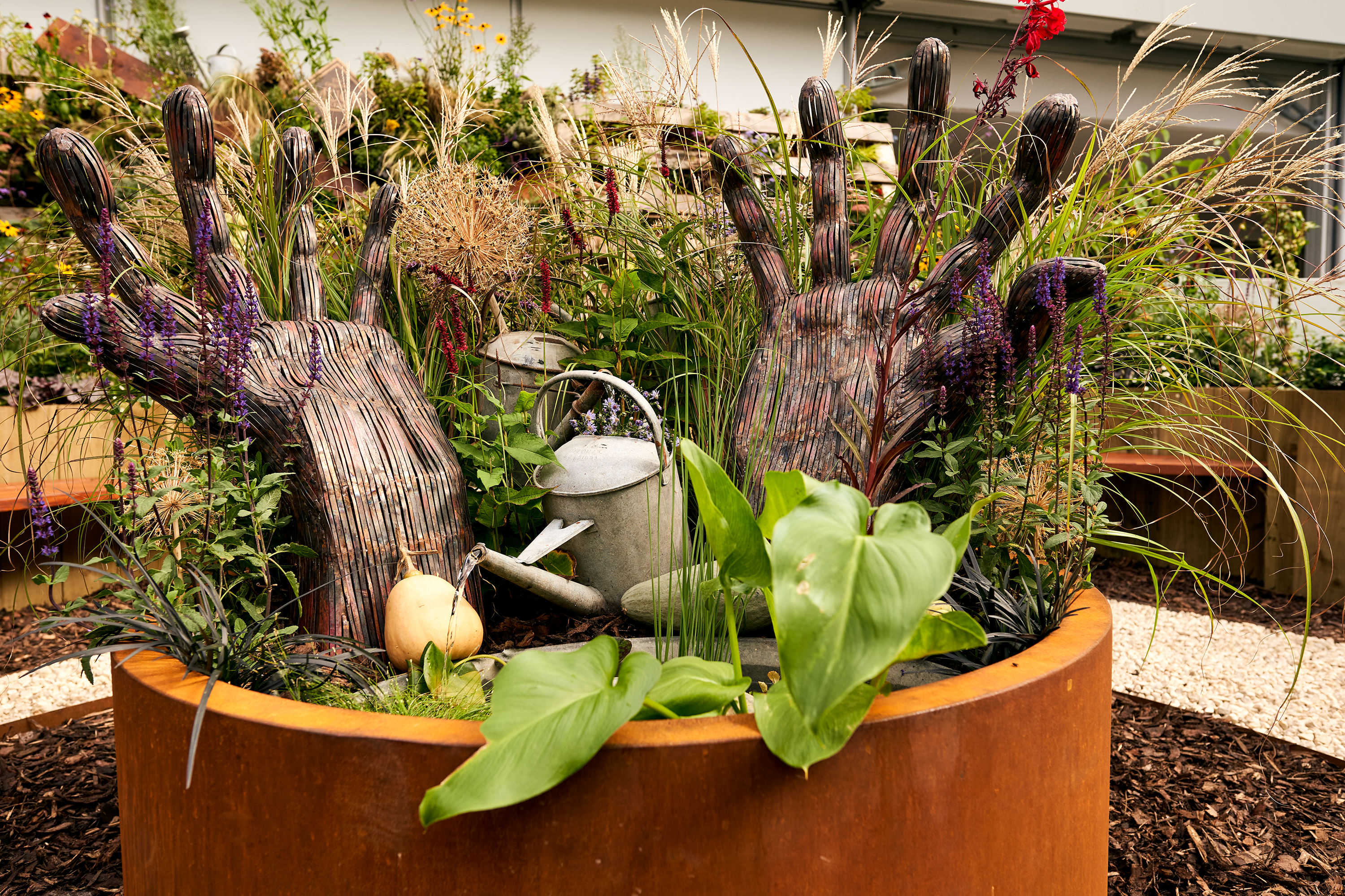 Plant pot with a variety of plants, flowers and hand installation in the middle