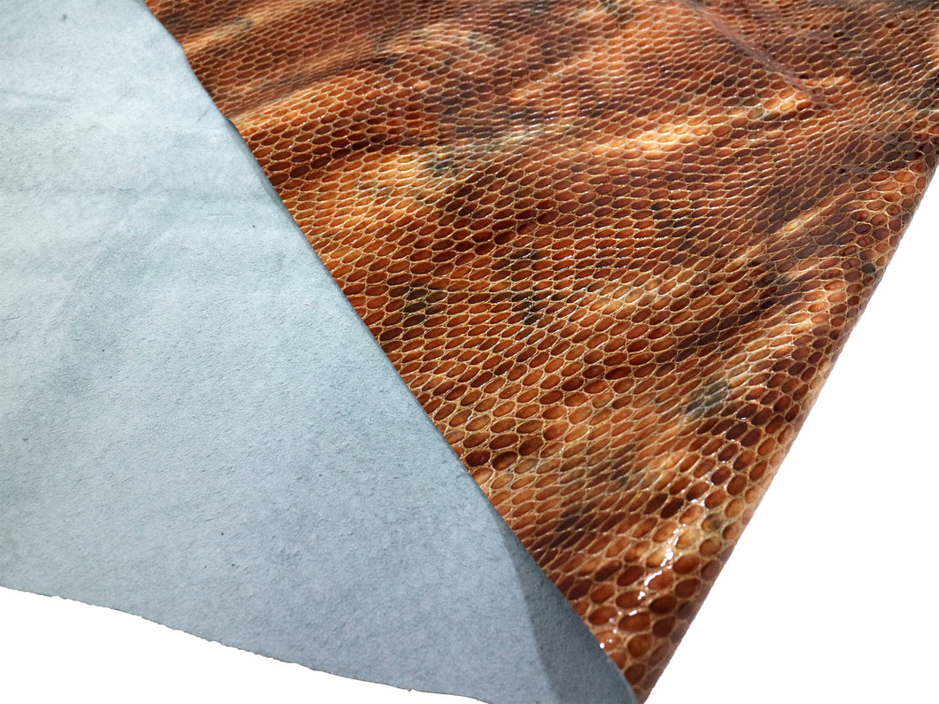 Brown and tan patent embossed snake print leather sheet sold by the square foot.
