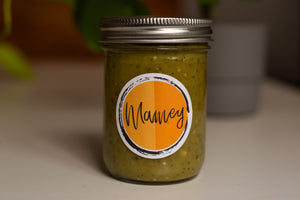 A small mason jar of salsa rests on top of a white table. The image is a close up of the small mason jar of salsa that is filled up with avocado tomatillo salsa and and lid on top is sealed. There is a circular Mamey brand sticker on the front of the small mason jar.