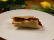 A white plate rests on a table with yellow tulips around the exterior of the plate. On top of the plate rests a miniature tamal with a red filling bursting out of the middle.