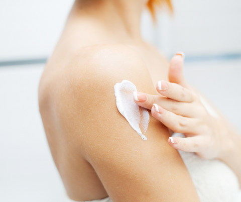 white woman applying lotion to her arm
