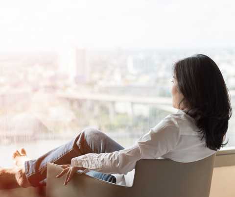 woman sitting down relaxing in front of a window with her feet up looking at the view