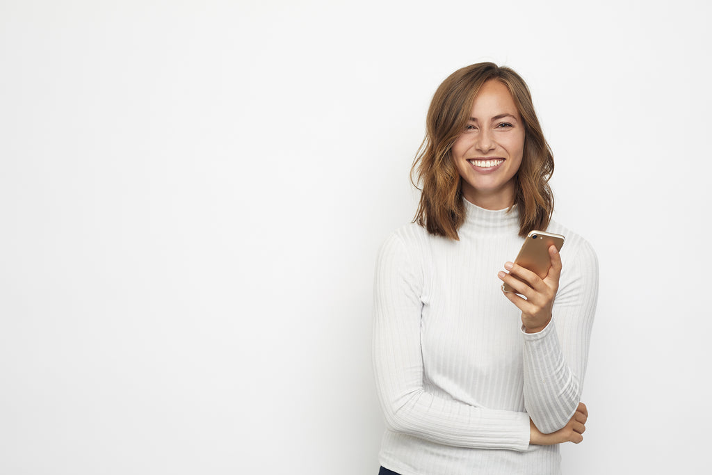 woman in white turtleneck holding iphone