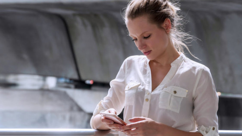 woman staring down at iPhone in a white blouse