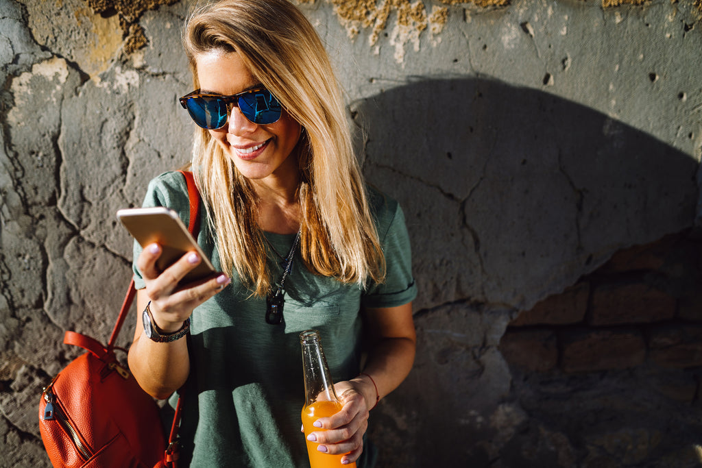 BLond woman in causal t-shirt looking down at iPhone