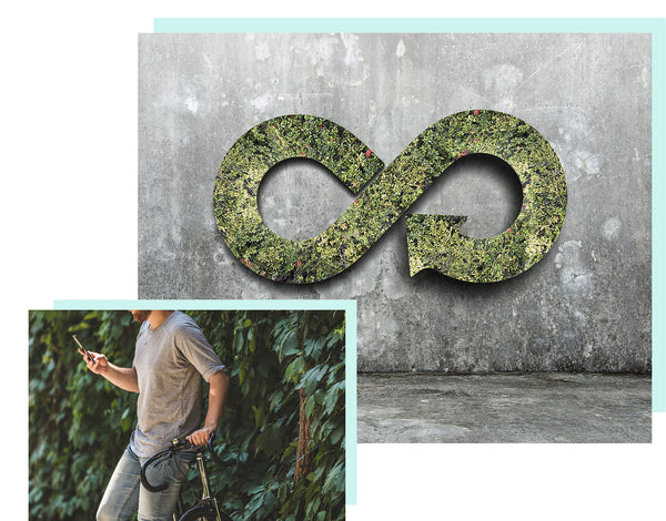 man texting while leaning on a bike with an infinity sign on green wall
