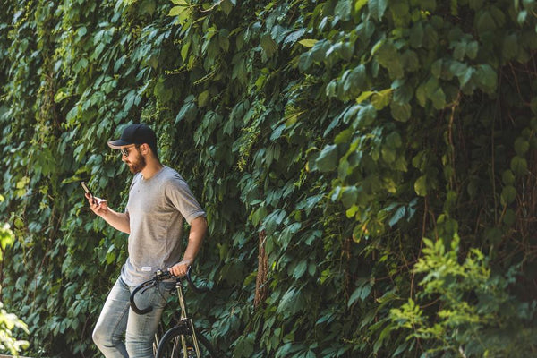 stylish casual guy leaning against a bicycle texting outside Frank Mobile
