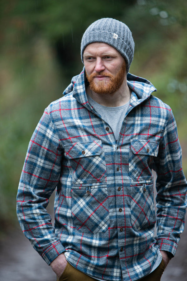 Hooded plaid shirt with multi pocket detail, designed to be slightly oversized. Colours are grey, blue and red. Brushed cotton fabric