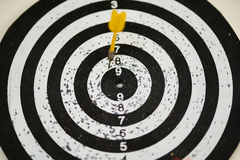 A yellow dart rests on a black and white target