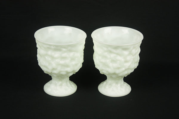 a couple of white vases sitting on top of a black table