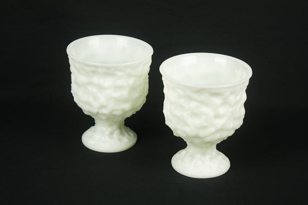 a couple of white vases sitting on top of a table
