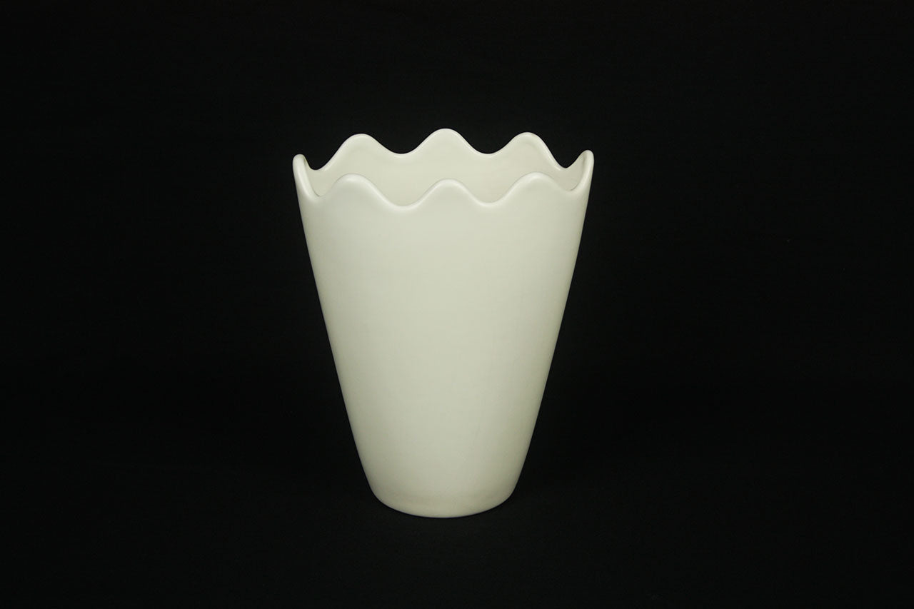 a white vase sitting on top of a black table