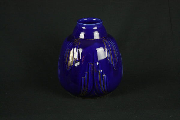 a blue vase sitting on top of a table