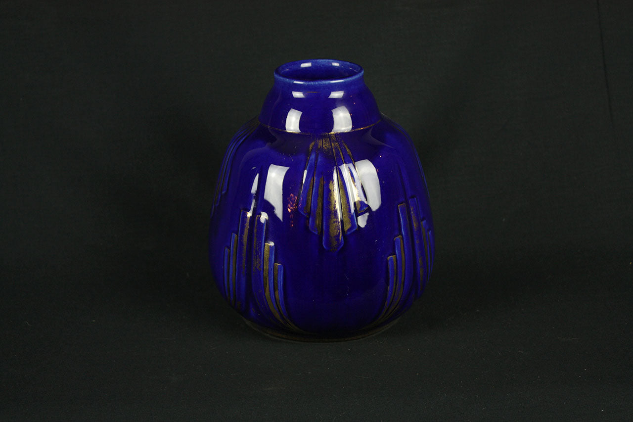 a blue vase is sitting in the dark