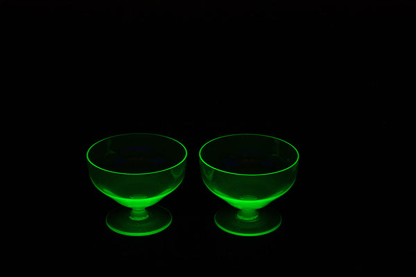 a close up of two glasses of water and a green cup