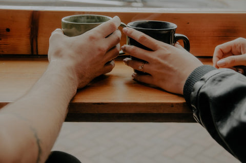 man and woman drinking coffee with rings