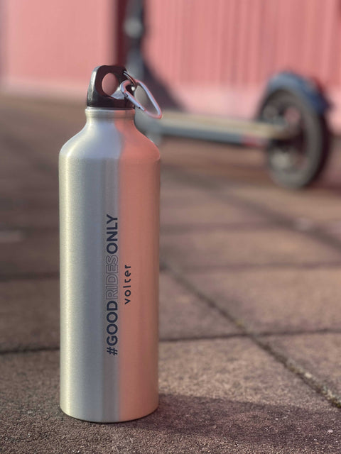 aluminium reusable water bottle on pavement with scooter