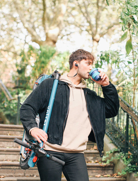 man carrying scooter folded over shoulder while drinking coffee