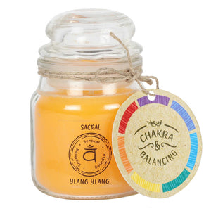 Balancing Chakra Candle in a min glass jar with stopper. Tied with a label that says Chakra Balancing. Candle is orangey yellow with a label on the jar that says Sacral - Ylang Ylang