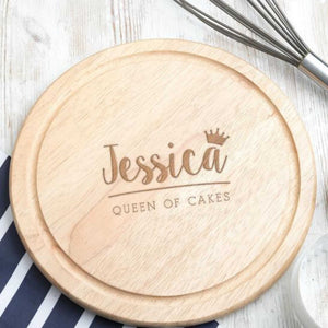 Round Wooden Bespoke Chopping Board, personalised with the slogan Queen of Cakes in the middle. Wood is lightish brown. Bespoke chopping board has also been personalised with the name Jessica in cute italic writing, with a small crown above the last letter. The board is pictured on a worktop on top of a striped tea towel and next to a metal whisk. Round wooden board could also be used as a baking board, a cheese board or a serving board.